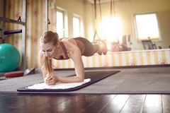 Young fit blond woman doing front planks stock photos