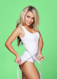 Young and fit blond woman measuring her waist Stock Photos