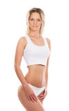 A young and fit blond woman in white lingerie Stock Photo