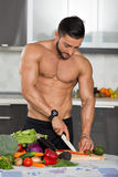 Young fit bodybuilder in the kitchen Royalty Free Stock Photography