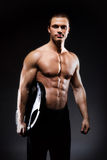 Young and fit bodybuildrer model on a dark background Stock Photos
