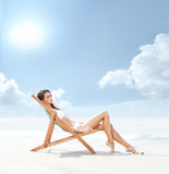 A young and fit brunette relaxing on a beautiful beach Stock Images