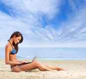A young and fit brunette relaxing on a beautiful beach Royalty Free Stock Photos
