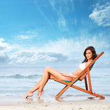 A young and fit brunette relaxing on a beautiful beach Royalty Free Stock Image