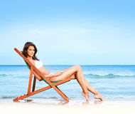 A young and fit brunette relaxing on a beautiful beach Stock Photo