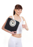 A young and fit brunette with scales and a bottle Royalty Free Stock Photo