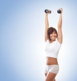 A young and fit brunette training with dumbbells Stock Photos