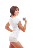 A young and fit brunette woman holding a dumbbell Stock Photography