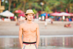 Young fit caucasion guy staying on the beach and Royalty Free Stock Photo