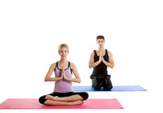 Young and Fit Couple. Beautiful couple doing yoga on a white background Royalty Free Stock Images