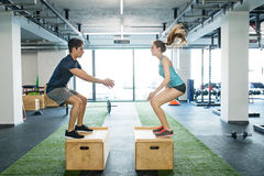 Young fit couple exercising in gym, doing box jumps. Stock Image