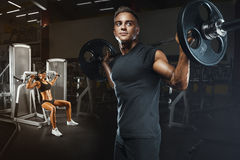 Young and fit couple in the gym doing workout. Group of women and men bodybuilders training on special sport equipment in the gym. Sport, bodybuilding Stock Photo