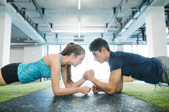Young fit couple in gym in plank position exercising core muscle. Beautiful young fit couple in modern crossfit gym doing strength training, exercising core Royalty Free Stock Photography