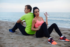 Young fit couple having break after workout outdoors Stock Photos
