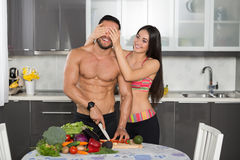 Young fit couple in the kitchen, cooking, cutting vegetables Royalty Free Stock Photography