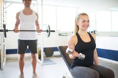 Young Fit Couple Lifting Barbells Inside the Gym. Happy Young Fit Couple Lifting Barbells While Looking at theirselves on the Mirror Inside the Gym Stock Image