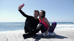 Young fit couple sitting near the beach holding phone and taking selfies posing. Happy boyfriend and girlfriend taking pictures.  stock footage