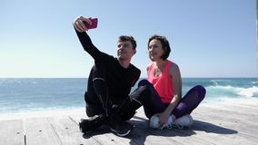 Young fit couple sitting near the beach holding phone and taking selfies posing. Happy boyfriend and girlfriend taking pictures.  stock video footage