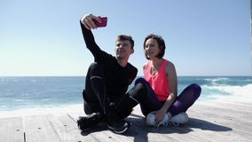 Young fit couple sitting near the beach holding phone and taking selfies posing. Happy boyfriend and girlfriend taking pictures. S. Low Motion stock video