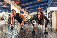 Attractive young woman and man do plank exercise in gym. Young fit couple of trainers doing plank exercise in modern gym royalty free stock photography