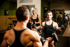 Young fit couple workout in fitness gym Stock Photos