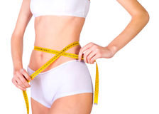 Young fit female measuring waist Stock Photography