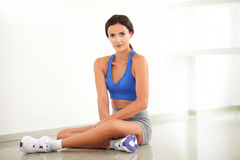 Young fit female smiling in sitting posture Royalty Free Stock Photos