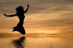 Young fit girl. Silhouette of young woman jumping against a sunset Royalty Free Stock Images