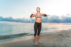 Young fit girl doing morning exercises on beach at sunrise royalty free stock photography