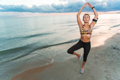 Young fit girl doing yoga exercises on beach at sunrise stock photo