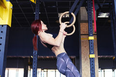 Young fit girl pulling up on a gimnastic rings Stock Images
