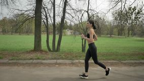 Young fit girl is running with earphones in park in summer, healthy lifestyle, sport conception, side view