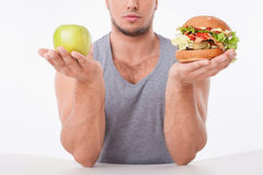 Young fit guy is choosing between healthy and Stock Photos