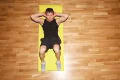 Young fit guy doing exercise in gym. Young sportsman doing abs basic crunch exercise on wooden floor, copy space left Royalty Free Stock Photo