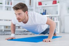 Young fit guy doing push ups in living room. Young fit guy doing push ups in the living room stock images