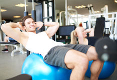 Young Fit Guy Doing Sit-ups on Exercise Ball. Handsome Young Fit Guy Smiling at the Camera While Doing Sit-ups on Exercise Ball Inside the Gym Stock Image
