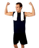 Young fit guy showing biceps. Towel around his neck Stock Image