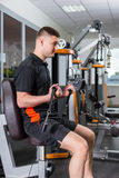 Young fit handsome man working out and doing exercises at gym Stock Photo