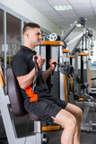 Young fit handsome man working out in gym room Stock Images