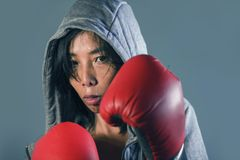 Young fit and healthy Asian Korean boxer woman in fitness top hoodie and boxing gloves posing cool badass attitude angry and defia. Nt in fight workout and gym royalty free stock photography