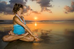 Young fit and healthy attractive woman practicing fitness and yoga in beautiful sunset beach in meditation and relaxation concept. Under amazing orange sky in Stock Photos