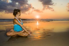 Young fit and healthy attractive woman practicing fitness and yoga in beautiful sunset beach in meditation and relaxation concept. Under amazing orange sky in Royalty Free Stock Images