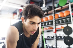 Young fit hispanic man in black sleeveless shirt in gym. Young fit hispanic man in black sleeveless shirt in modern crossfit gym resting Royalty Free Stock Images