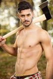 Young fit lumberjack. Holding an ax over his shoulder Royalty Free Stock Image
