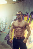 Young fit macho man posing in front of graffiti wall Stock Images