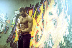 Young fit macho man posing in front of graffiti wall Royalty Free Stock Photography