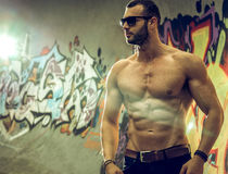 Young fit macho man posing in front of graffiti wall Royalty Free Stock Image