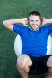 Young fit male athlete on workout ball. Young fit male on workout ball on athletic field Royalty Free Stock Photos