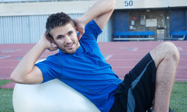 Young fit male athlete on workout ball Stock Images