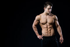 Young and fit male model posing his muscles looking downwards  on black background. Man showing his six pack abs on dark background Royalty Free Stock Photo